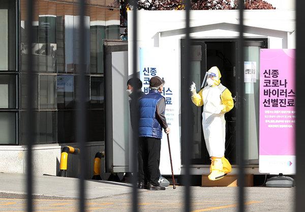 2월 9일 서울 중구 국립중앙의료원 선별진료소 앞에서 방역복을 입은 의료진이 한 시민을 안내하고 있다. 이날 신종코로나 확진 환자는 3명이 추가돼 총 27명이 됐다.  뉴스1