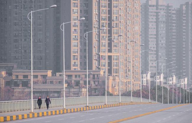 1월 28일 중국 우한에서 마스크를 쓴 사람들이 인적 드문 거리를 걷고 있다. [뉴시스]
