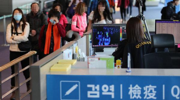 인천국제공항 제1터미널 입국장에서 질병관리본부 국립검역소 직원들이 열화상 카메라로 중국 공항에서 출발해 인천공항에 도착한 승객들의 체온을 측정하고 있다. [사진공동취재단]
