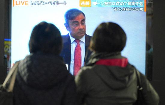 도쿄 시민들이 1월 8일 카를로스 곤의 탈주극을 다룬 방송 뉴스를 보고 있다. [뉴시스]