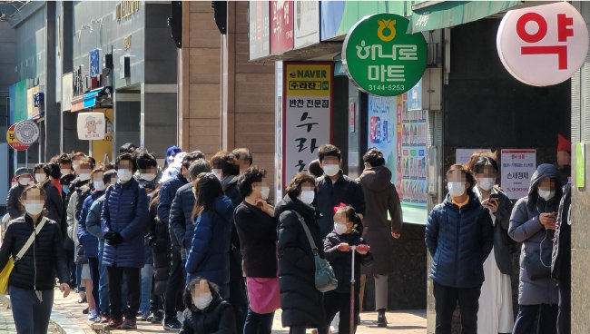 3월 14일 서울 마포구의 한 약국 앞에 평일에 마스크를 사지 못한 시민들이 줄지어 서 있다. [뉴스1]