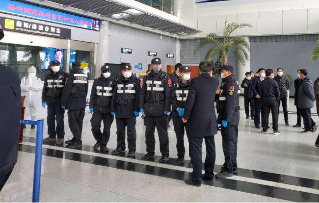 2월 25일 중국 산둥성 웨이하이국제공항에서 경찰과 공항 관계자들이 한국발 입국자를 이송하기 위해 대기하고 있다. [뉴시스]