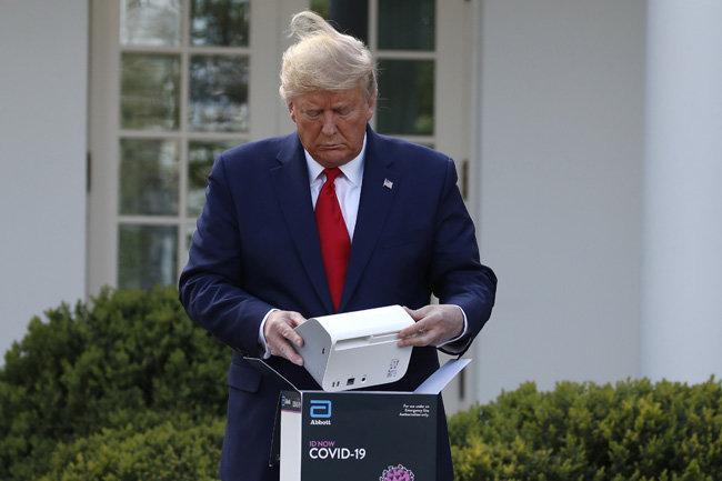 도널드 트럼프 미국 대통령이 3월 30일 미국 백악관에서 진행한 코로나19 브리핑 도중 미국 업체가 개발한 '5분 진단키트'에 대해 설명하고 있다. [AP=뉴시스]