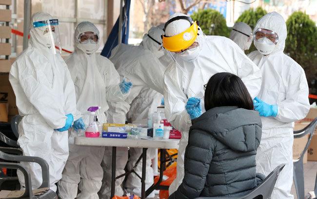 3월 12일 오후 신종 코로나바이러스 집단 감염증 확진자가 나온 서울 구로구 보험사 콜센터 건물에서 한 시민이 검체 검사를 받고 있다. [전영한 동아일보 기자]