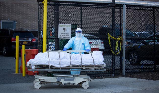 4월 6일 미국 뉴욕의 한 병원에서 한 의료인이 코로나19로 숨진 피해자의 시신을 이송하고 있다. [뉴시스]