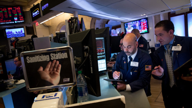 3월 11일(현지 시간) 미국 뉴욕 증권거래소에서 주식 트레이더들이 모니터를 들여다보며 일하고 있다. 이날 다우존스30산업평균지수는 전날보다 1464.94포인트(5.86%) 하락했다. [뉴욕=AP 뉴시스]