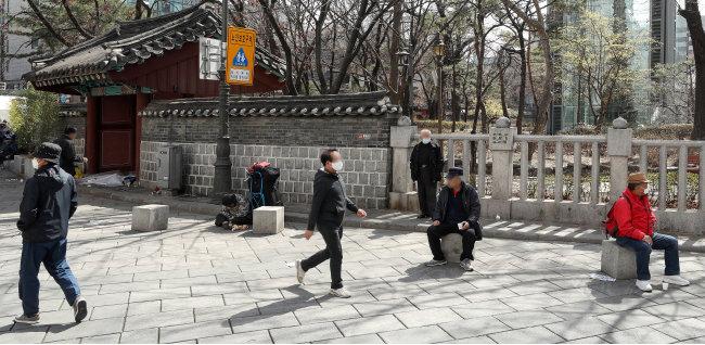 3월 20일 시민들이 마스크를 착용하고 서울 종로구 탑골공원 앞길을 걸어가고 있다. [뉴시스]