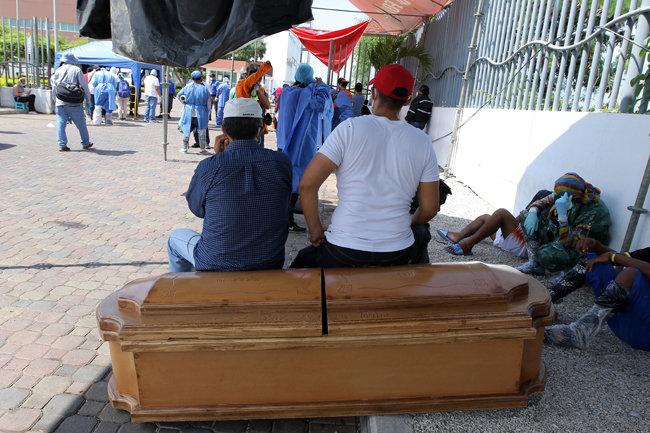에콰도르 화장장에서 관에 걸터앉은 채 순서를 기다리는 유족들. [GETTYIMAGES]