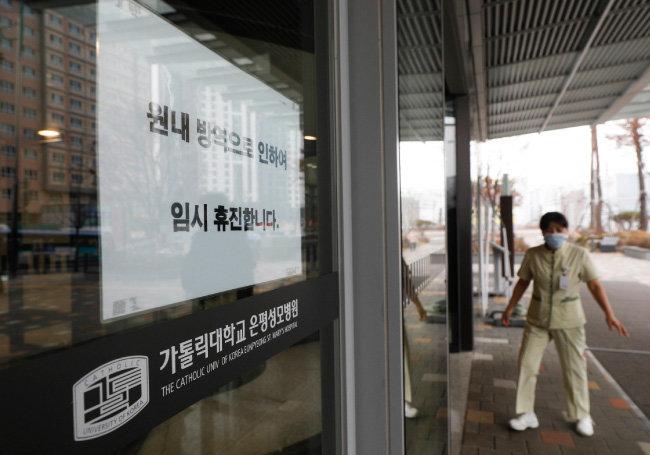 2월 21일 코로나19 확진자가 발생한 서울 은평성모병원 유리문에 임시 휴진 안내문이 붙어 있다. 은평성모병원은 3월 초까지 17일간 폐쇄됐다. [뉴시스]