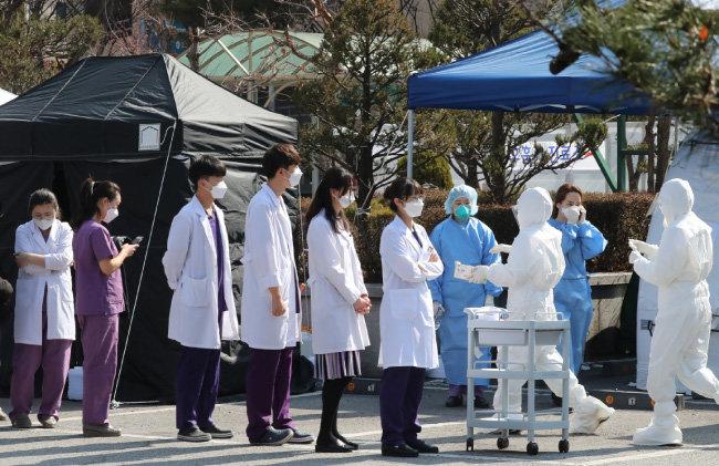 코로나19 집단 감염이 발생한 분당제생병원 의료진이 3월 6일 병원 주차장에 마련된 선별진료소에서 코로나19 진단 검사를 받으려고 대기하고 있다. [홍진환 동아일보 기자]