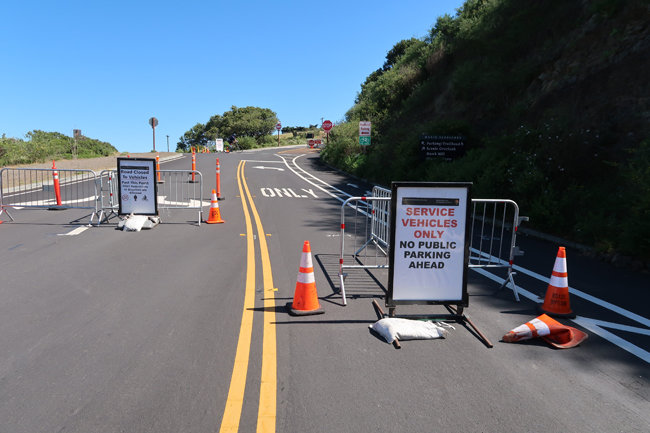 금문교와 샌프란시스코 전경이 내려다보이는 산길 도로 입구에  차량 통행 및 주차금지 안내 표지판이 놓여 있다.