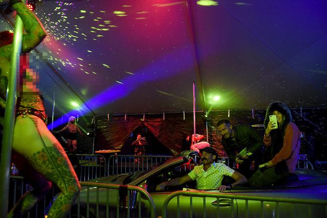 댄서들은 마스크를 착용하고 춤을 추며 관객들은 차에 앉아 환호한다. [GETTYIMAGES]