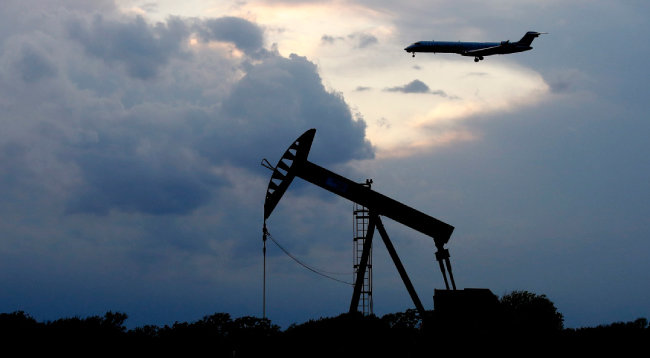 석양을 배경으로 한  미국 오클라호마주  오클라호마시에 있는  석유 시추 시설(펌프잭).  저무는 석유 시대를  상징하는 듯하다. [뉴시스]