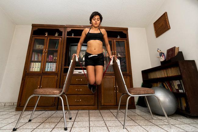 멕시코, 과달라하라/스포츠 클라이밍 선수 마리아 페르난다 곤잘레스가 자기 집에서 의자를 이용해 근육 강화 훈련을 하고 있다. [GETTYIMAGES]