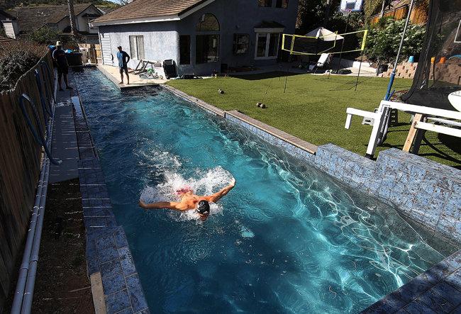 미국, 샌디에고/미국 국가대표 수영선수 마이클 앤드류가 집 수영장에서 아버지가 지켜보는 가운데 물살을 가르고 있다. [GETTYIMAGES]
