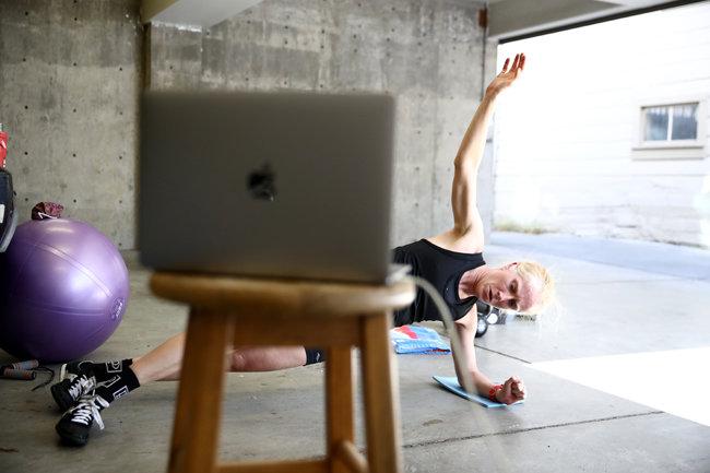 미국, 라구나스/트라이애슬론 선수 사라 피암피아노가 자기집 차고에서 노트북을 보며 스트레칭을 하고 있다. [GETTYIMAGES]