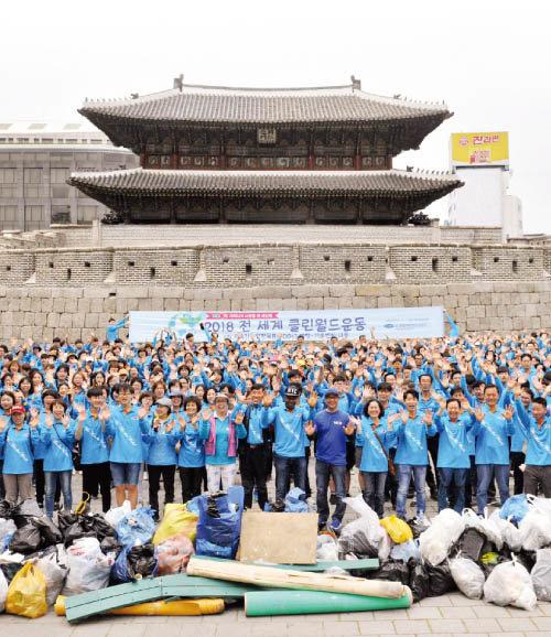 위러브유 회원들이 서울 종로구에서 개최한 클린월드운동을 마치고 환하게 웃고 있다. 그 뒤로 서울의 랜드마크인 흥인지문이 보인다.