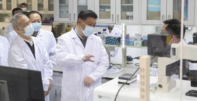 시진핑 중국 국가주석(가운데)이 3월 2일 베이징 중국 군사의학연구원을 방문해 연구진과 얘기하고 있다. 시 주석은 이 날 코로나19 백신 개발에 박차를 가할 것을 주문했다. [뉴시스]