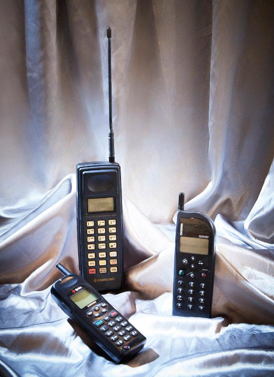 1997년 미국에 수출된 최초의 CDMA 휴대전화 SCH-1000. 제조사 삼성. (왼쪽 아래)   1988년 시판된 최초의 '메이드 인 코리아' 휴대전화 SH-100. 제조사 삼성. (왼쪽 위) 1995년 유럽에 수출된 첫 국산 디지털 전화기 MX-3000. 제조사 맥슨. (오른쪽)