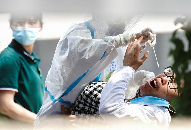 6월 16일 중국 베이징시의 한 검사시설에서 방역복을 착용한 간호사가 코로나19 검사를 하고 있다.