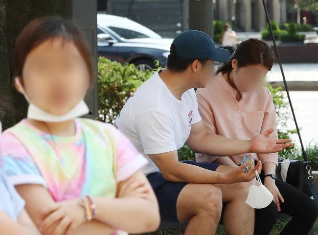 14일 오후 서울 종로구 광화문 인근에서 마스크를 내린 시민들이 벤치에 앉아 있다. [뉴스1]
