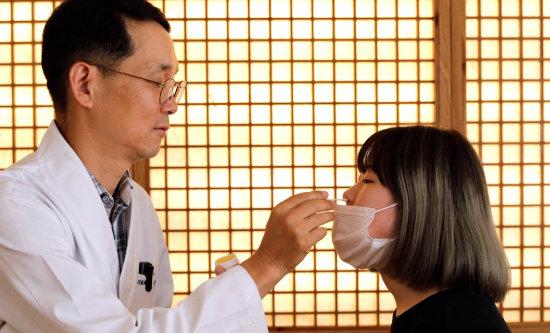 웅담을 넣어 만든 비염고를 환자 코 안에 바르고 있다. [박해윤 기자]