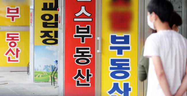 6월 17일 경기 수원시 한 부동산중개업소 앞을 지나가는 시민들의 모습. [뉴스1]