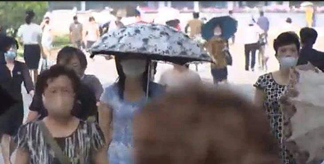 양산을 든 여성이 마스크를 쓴 채 걷고 있다.