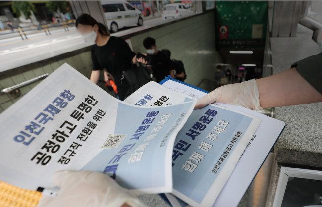 6월 30일 서울 마포구 서울지하철 2호선 홍대입구역 앞에서 인천국제공항공사 직원들이  보안검색요원 정규직 전환 절차를 문제 삼는 내용의 전단지를 배포하고 있다. [뉴스1]