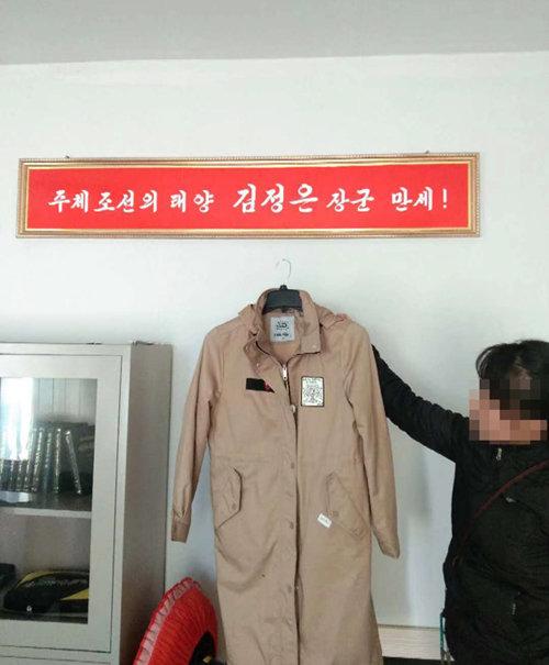 북한 근로자가 평양의 한 공장에서 해외 유명 브랜드 의류를 들고 있다.