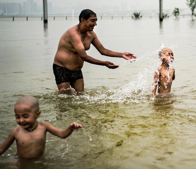 7월 10일 중국 후베이(湖北)성 우한(武漢)시 양쯔강변에서 물놀이 하는 가족.