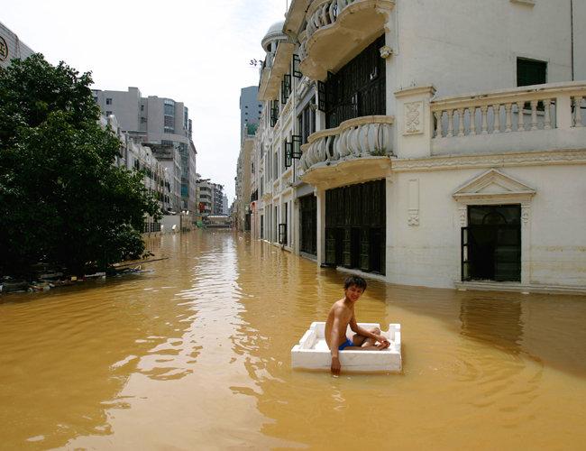 6월 24일 중국 광시(廣西)좡족자치구 우저우(梧州)시에서 한 주민이 스티로폼 박스에 몸을 맡긴 채 흙탕물에 잠긴 도심을 지나고 있다.