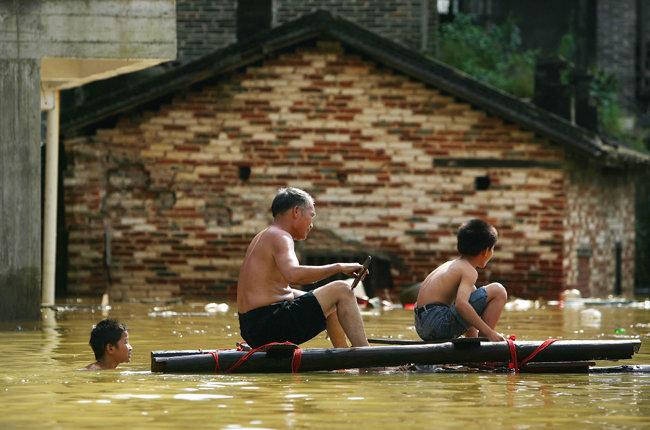 6월 25일 우저우(梧州)시에서 뗏목에 탄 주민들이 노를 젓고 있다.