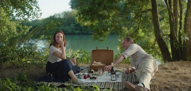 영화 '파리로 가는 길'에서 주인공들은 풀밭 위 간식부터 고급 레스토랑에서의 정찬까지 다양한 식사를 즐긴다.