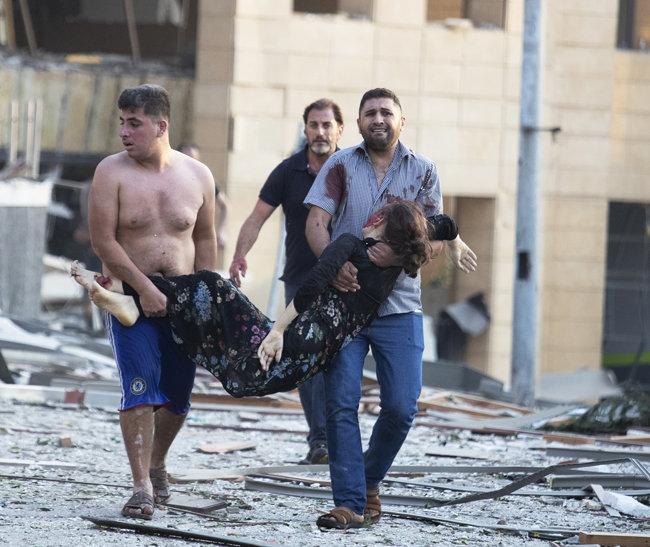 4일 베이루트 시민들이 부상자를 안은 채 대피하고 있다.
