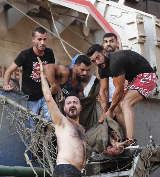 4일 시민들이 폭발로 다친 선원을 후송하고 있다.