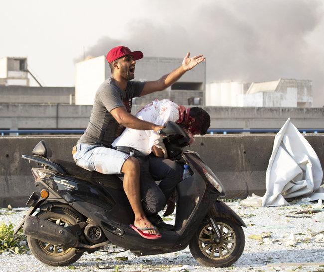 4일 한 남성이 부상자를 오토바이에 실은 채 탄식하고 있다.