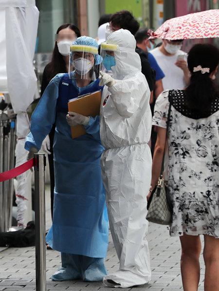 8월 19일 서울 성북구에 마련된 코로나19 선별진료소에서 의료진이 대화를 나누고 있다. [뉴스1]
