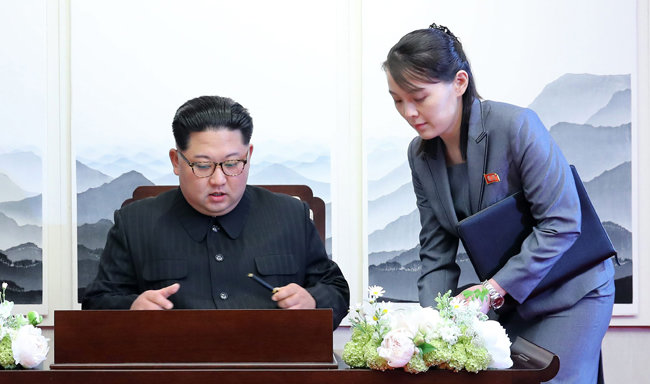 김정은 북한 국무위원장이 2018년 4월 27일 판문점에서 열린 '한반도의 평화와 번영, 통일을 위한 판문점 선언' 서명식에서 김여정 노동당 제1부부장의 도움을 받아 선언문에 서명을 하고 있다. [한국사진공동취재단]