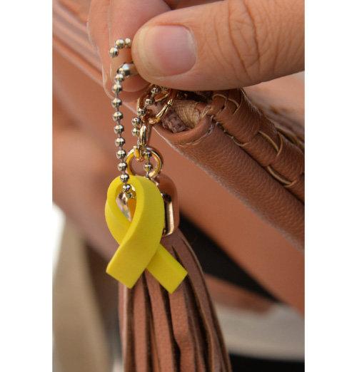 세월호 참사 5주기인 2019년 4월 16일 울산시 남구 롯데호텔 정문 앞에 마련된 세월호 희생자 분향소에서 시민들이 가방에 노란 리본을 달고 있다.  [뉴시스]