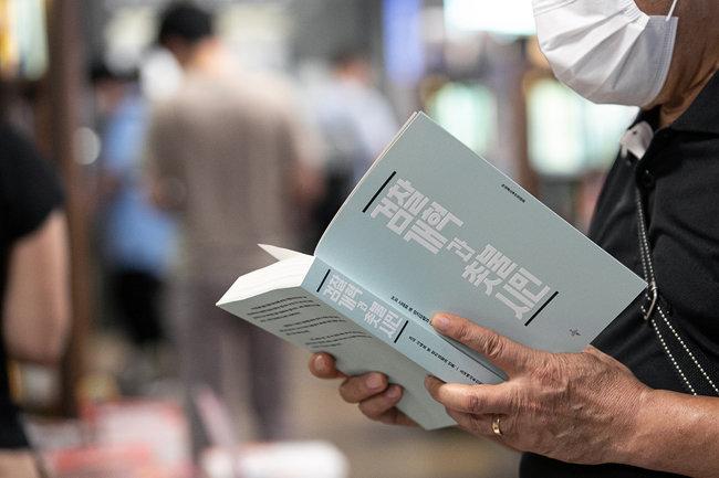 8월 12일 서울 한 대형서점에서 한 시민이 '검찰개혁과 촛불시민'(조국 백서)을 살펴보고 있다. [뉴스1]
