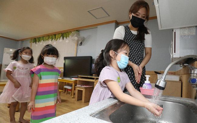 코로나19 자가격리자와 함께 생활할 경우 집 안에서도 밀접 접촉 시 마스크를 쓰고 손 씻기를 생활화해야 한다. 6월 1일 대구 달서구 본영어린이집에서 어린이들이 선생님에게 손 씻는 법을 배우고 있다. [뉴스1]