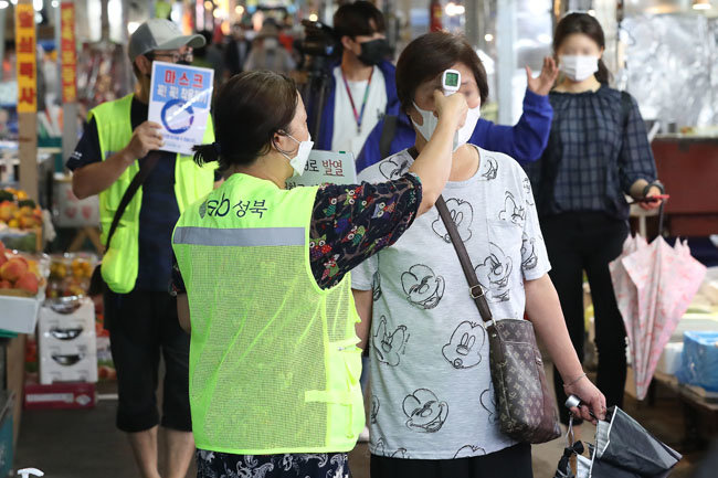 2일 오후 서울 성북구 한 전통시장에서 시장 관계자가 출입 손님 체온을 측정하고 있다.  [뉴스1]