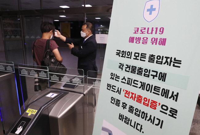 6일 오전 서울 여의도 국회의사당 입구에서 출입자가 발열검사를 받고 있다. [뉴스1]