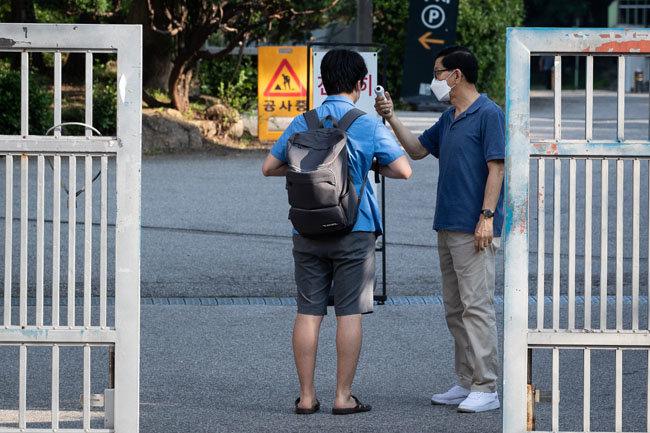 8월 26일 서울 한 고등학교에서 고3 학생이 등교 전 교문에서 체온을 확인받고 있다. [뉴스1]