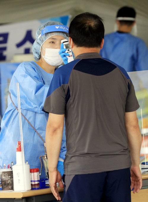 7월 19일 광주 서구청에 마련된 코로나19 선별진료소에서 한 시민이 피부적외선체온계로 체온 검사를 받고 있다. [ 박영철 동아일보 기자]