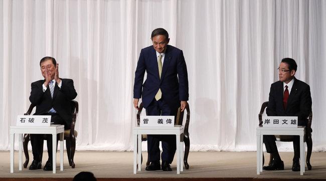 """9월 8일 일본 도쿄 자민당사에서 열린 총재 선거 소견 발표장에서 일어나 인사하고 있는 스가 요시히데 관방장관(가운데). 그는 이 자리에서 """"아베 신조 총리의 노선을 계승하겠다""""고 밝혔다. [도쿄=AP 뉴시스]"""