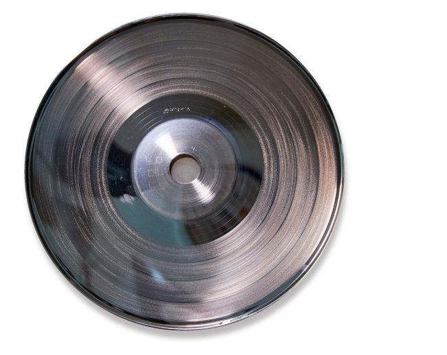 가수 김목경 1집 LP를 찍어낸 금속 원판(stamper). 이 원판을 고열로 LP에 찍으면 음반이 만들어진다. 보통 금속 원판(stamper)은 쉽게 마모되어 한 장당 750장 정도를 LP를 프레싱하는 것으로 알려져 있다. 그래서 수집가들은 처음 제작해 골이 깊어 음질이 좋은 초반 LP를 선호한다.