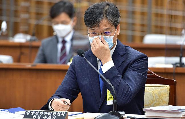 조성대 중앙선거관리위원 후보자가 22일 서울 여의도 국회에서 열린 인사청문회에서 마스크를 만지고 있다. [김재명 동아일보 기자]