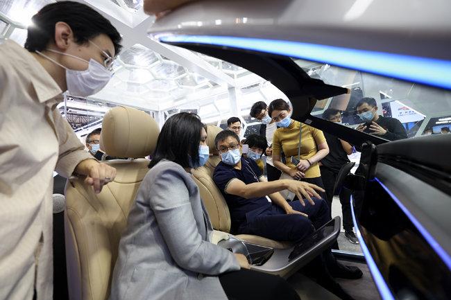 9월 27일 베이징모터쇼에서 마스크를 착용한 관람객들이 화웨이에서 선보인 인공지능 조종석에 앉아 시험 운전을 하고 있다.  [GettyImage]